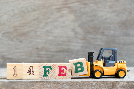 Toy forklift hold letter block B to complete word 14 Feb on wood background (Concept for 14 february that is Valentine 's day)