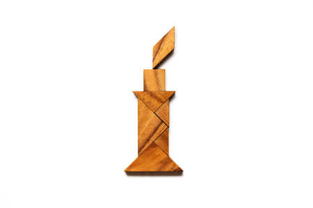 Wood tangram puzzle in candle shape on white background (Concept for hope, idea thinking)