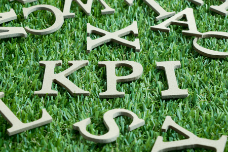 Wood letter in word KPI (Abbreviation of key performance indicator) on artificial green grass with English alphabet background