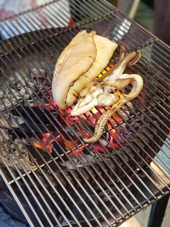 Fresh squid cook by grill on stove that use charcoal background (Street food)