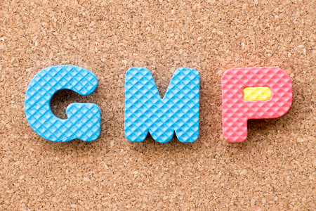 Color toy foam alphabet in word GMP (Abbreviation of Good Manufacturing Practice) on cork board background