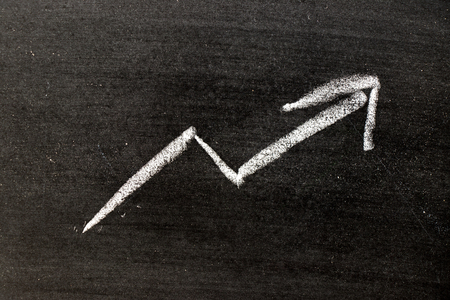 White color hand drawing chalk in arrow upward shape on black board background (Concept of revenue increase, stock or business growth)