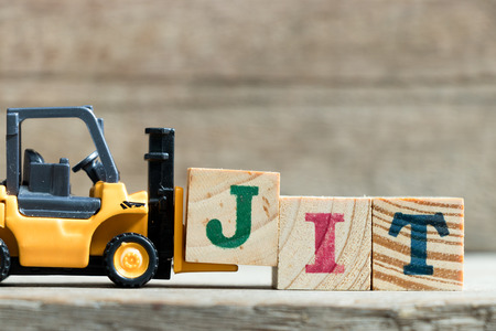 Toy yellow forklift hold letter block J to complete word JIT (Abbreviation of Just in time)on wood background Stockfoto