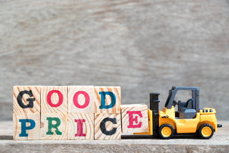 Toy forklift hold letter block E to complete word good price on wood background