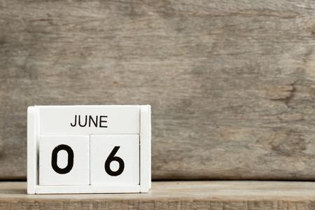 White block calendar present date 6 and month June on wood background Standard-Bild
