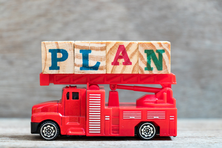 Red fire truck hold letter block in word plan on wood background