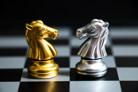 Gold horse in chess game face with the another silver team on black background (Concept for company strategy, business victory or decision)