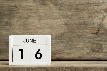White block calendar present date 16 and month June on wood background Stock Photo