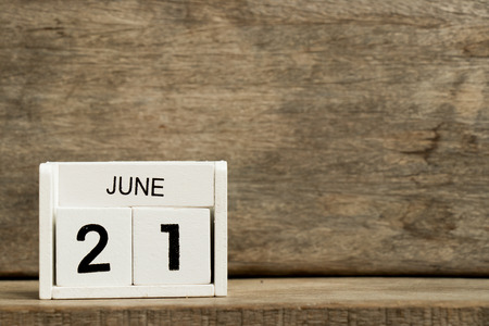 White block calendar present date 21 and month June on wood background