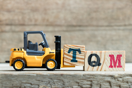 Toy yellow forklift hold letter block T to complete word T (Abbreviation of total quality management)on wood background