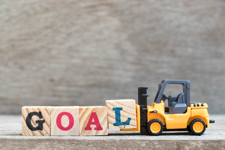 Toy forklift hold letter block L to complete word goal on wood background Stock Photo