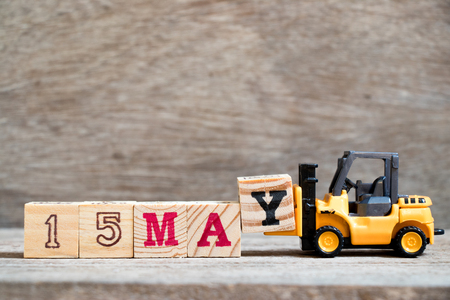 Toy forklift hold block Y to complete word 15 may on wood background (Concept for calendar date for month May)