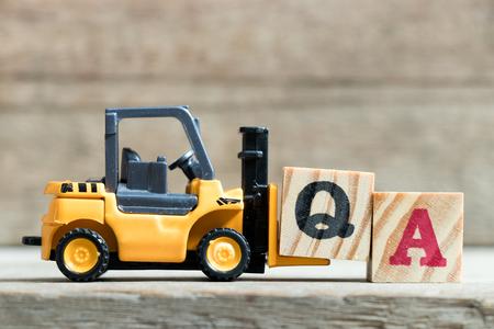 Carretilla elevadora amarilla de juguete mantenga el bloque de letras Q para completar la palabra QA (abreviatura de garantía de calidad o pregunta frecuente) sobre fondo de madera