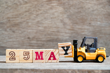 Toy forklift hold block Y to complete word 25 may on wood background (Concept for calendar date for month May) Archivio Fotografico