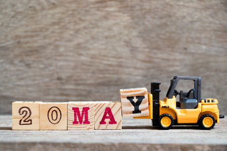 Toy forklift hold block Y to complete word 20 may on wood background (Concept for calendar date for month May)