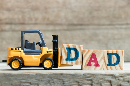 Toy yellow forklift hold letter block D to complete word dad on wood background (Concept of father day) Stock Photo