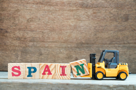 Yellow toy forklift hold letter block N to complete word Spain on wood background