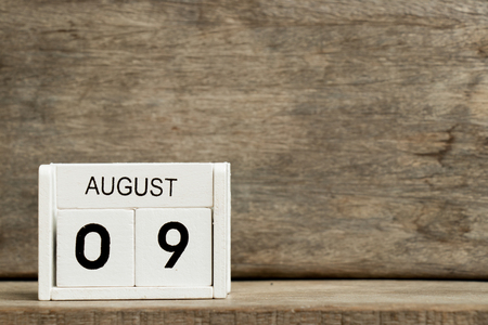 White block calendar present date 9 and month August on wood background