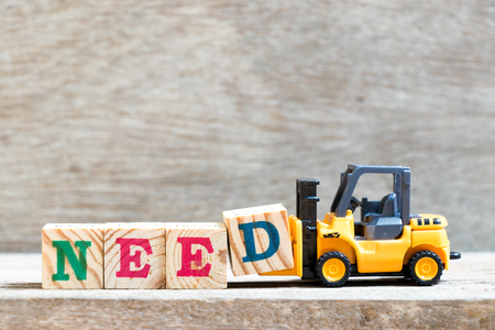 Toy forklift hold letter block D to complete word need on wood background Reklamní fotografie
