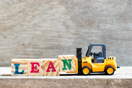 Toy forklift hold letter block n to complete word lean on wood background