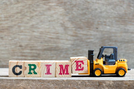 Toy forklift hold letter block E to complete word crime on wood background Stock Photo