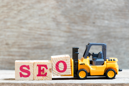 Toy forklift hold letter block O to complete word SEO (abbreviation of Search Engine Optimization) on wood background