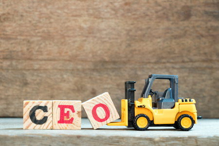 Yellow toy forklift hold letter block O to complete word CEO (abbreviation of Chief Executive Officer) on wood background