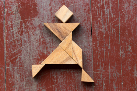 Tangram puzzle in joyful man running shape on red old wood background