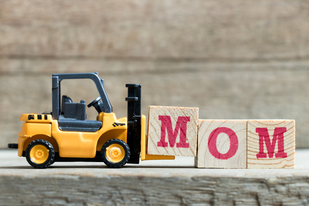 Toy yellow forklift hold letter block M to complete word MOM on wood background (Concept for mother s day)