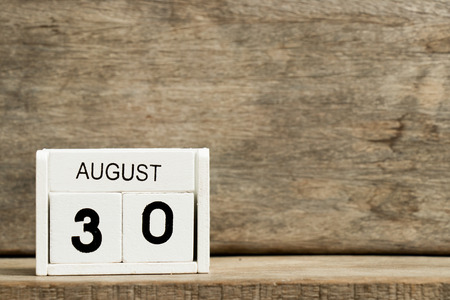 White block calendar present date 30 and month AUGUST on wood background Banco de Imagens