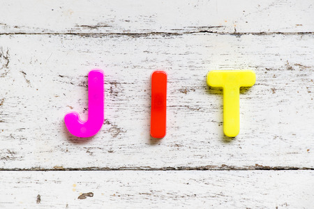Color alphabet in word JIT (Abbbreviation of Just in time) on grunge old white wood background