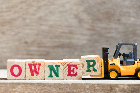 Toy forklift hold letter block R in word owner on wood background