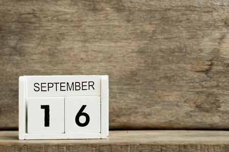 White block calendar present date 16 and month September on wood background