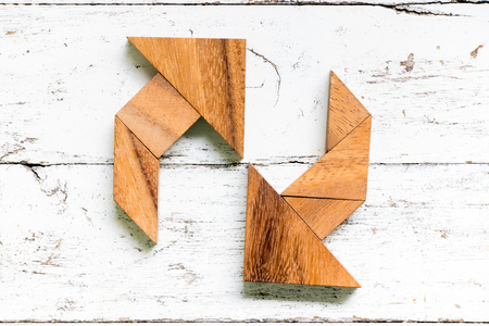 Tangram puzzle in circulate arrow shape on old white wood background (concept for refresh, reload or recycle) Reklamní fotografie