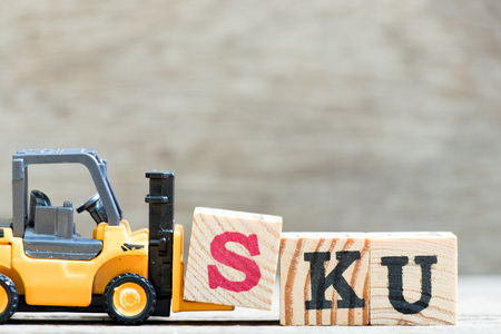 Toy forklift hold letter block S in word SKU (abbreviation of stock keeping unit) on wood background Stock Photo
