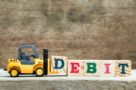 Yellow toy forklift hold letter block D to complete word debit on wood background