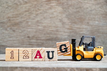 Toy forklift hold block G to complete word 12 aug on wood background (Concept for calendar date in month August)