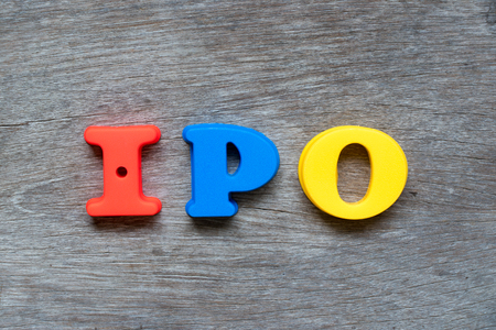 Colorful plastic alphabet in word IPO (Abbreviation of Initial Public Offering) on wood background Standard-Bild