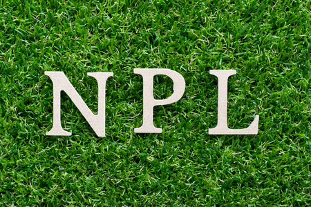 Wood alphabet in word NPL (abbreviation of Non Performing Loan, Non-Patent Literature) on artificial green grass background