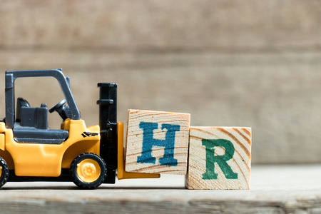 Toy yellow forklift hold letter block H to complete word HR (Abbreviation of Human resource)on wood background