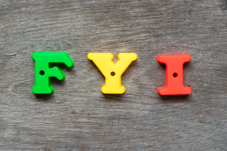 Colorful plastic alphabet in word FYI (Abbreviation of for your information) on wood background