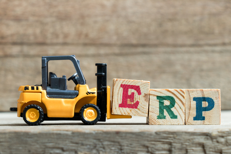 Toy yellow forklift hold letter block E to complete word ERP (Abbreviation of Enterprise Resource Planning)on wood background Reklamní fotografie