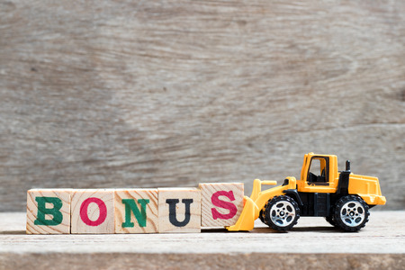 Toy forklift hold letter block s to complete word bonus on wood background
