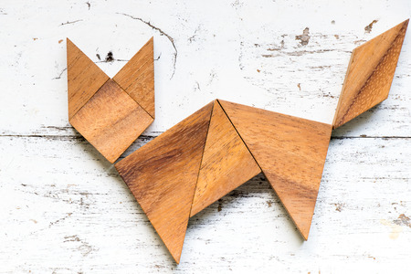 Tangram puzzle in cat shape on old white wood background