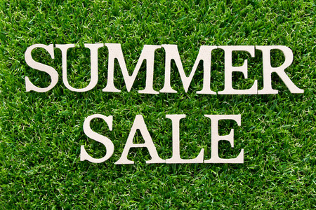 Wood alphabet in word summer sale on artificial green grass background Foto de archivo