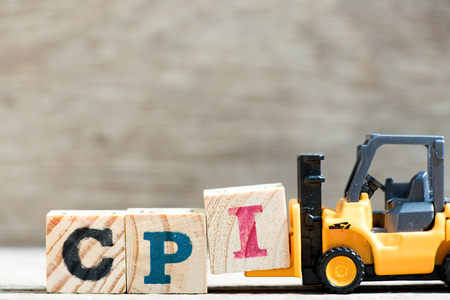 Toy forklift hold letter block I in word CPI (abbreviation of Consumer Price Index) on wood background