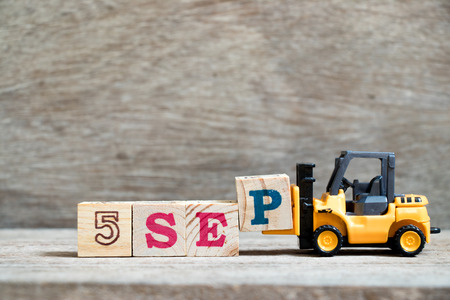 Toy forklift hold block P to complete word 5 sep on wood background (Concept for calendar date in month September)