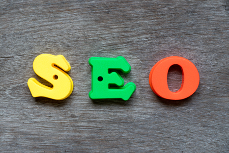 Colorful plastic alphabet in word SEO (Abbreviation of search engine optimization) on wood background