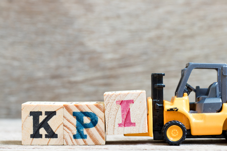 Toy forklift hold lette block I to complete word KPI (Abbreviation of Key performance indicator) on wood background Stok Fotoğraf - 106021003