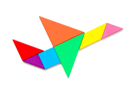 Color wood tangram puzzle in airplane shape on white background 免版税图像